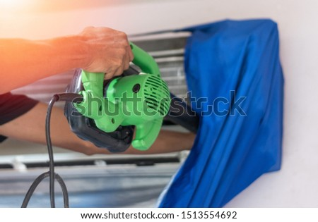 Air Conditioning Technician cleaning air conditioner in house. A/C or AC is fixed or maintenance.