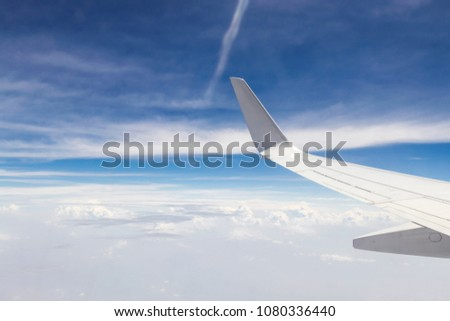 aircraft Wing and blue sky with clouds , view from the airplane window. #1080336440