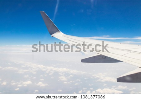 aircraft Wing and blue sky with clouds , view from the airplane window. #1081377086