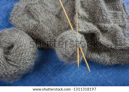 Вall and skein of gray mohair yarn, knitted scarf and bamboo knitting needles on blue background, close-up