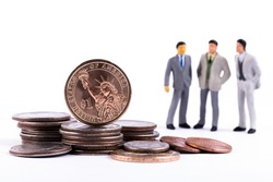 1 American dollar coin, other coins on a white background and three figurines of symbolic businessmen