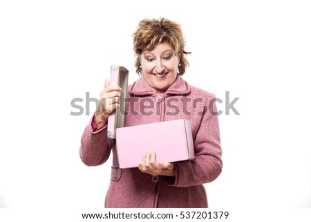 An adult woman opens a pink box surely a gift and looks inside isolated on white background