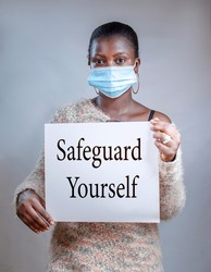 An African young woman wearing nose mask with a white placard with a health safety caution message SAFEGUARD YOURSELF