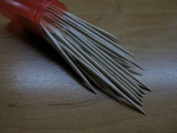 An armful of small toothpicks in the red container