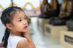 An Asian girl, 2-3 years old, standing to pay respect