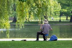An Asian male street performer plays a string instrument in Boston Public Garden, in Boston,Massachusetts.