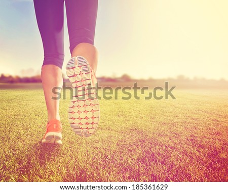 an athletic pair of legs on grass during sunrise or sunset done with a soft vintage instagram like filter