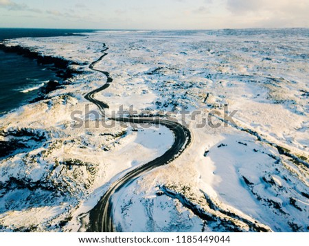 An Icelandic devious road covered by snow in Winter in Iceland. It is aerial scene in morning. The road go along the coast and ocean. It is a way to travel and adventure in Iceland.
