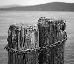 An old and worn mooring on a pier in Lake Trasimeno, consisting of two wooden pylons tied with a rusty iron chain. A poetic symbol of connection, bonding, eternal love, aging together.