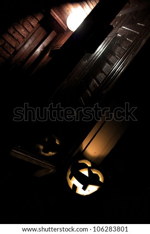 An old Jack-O-Lantern sits aglow on the window of porch.