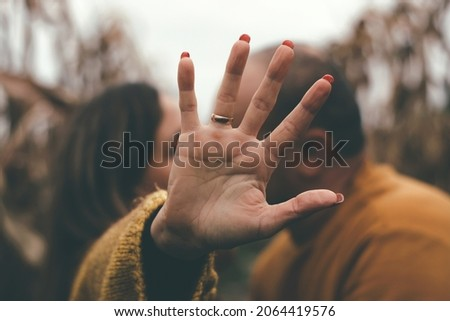 An open palm behind which the couple kisses