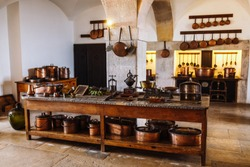 Ancient copper tableware stands in the kitchen on a larger wooden table in the palace da Pena, Sintra, Lisbon, Portugal