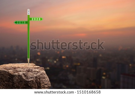 2020 and 2019 direction sign plate with green pencil on rock mountain over cityscape on warm light sundown, Business strategy planning concept, Happy new year 2020 calendar cover #1510168658