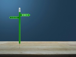 2021 and 2020 direction sign plate with green pencil on wooden table over light blue gradient background, Business happy new year planning concept