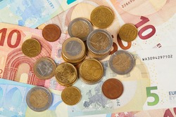 20, 10 and 5 Euros in paper money and various coins cents close up