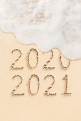 2020 and 2021 handwritten numbers on sand, beach and ocean wave on background. New Year concept photo
