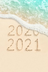 2021 and 2020 handwritten on sand, beach and soft ocean wave on background. New Year concept photo