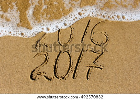2016 and 2017 year written on sandy beach sea. #492570832