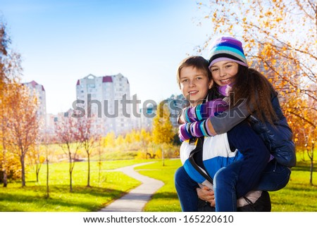 10 and 11 years old couple of school kids, boy an girl in warm autumn clothes