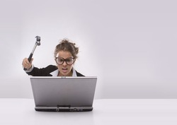 Angry brunette businesswoman with hammer and glasses against laptop