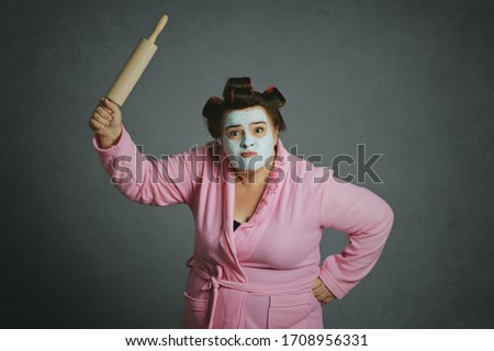 angry humorous overweight woman fighting holding a pastry roller with green beauty mask and hair curlers wearing pink bathrobe on gray studio background
