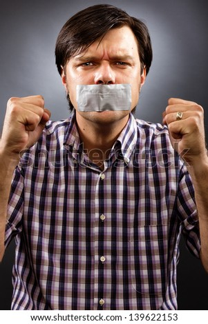 Angry  young man with duct tape over his mouth against gray background. Conceptual image - stock photo