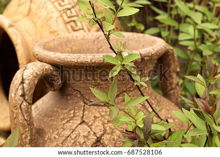 Antique cracked clay terracotta amphora in the garden on green background. Blurred.