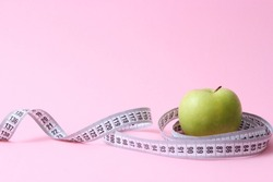 apple and centimeter tape on a colored background with a place for inserting the text. minimalism. concept diet, healthy diet, fat burning, calories.