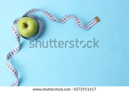 apple and centimeter tape on a colored background with space for text, top view. concept sport, diet, fitness, plan, healthy eating.