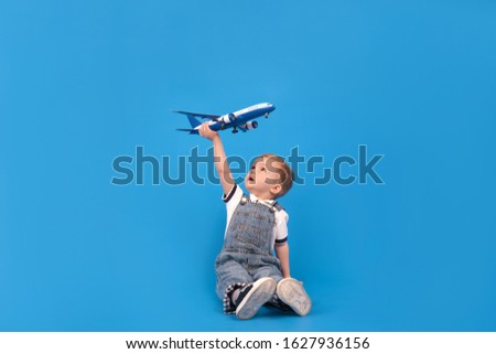 Рappy child sits holding plane in his hand and imagining how he is flying on plane on blue background. Imagination, creativity and concept ideas.
