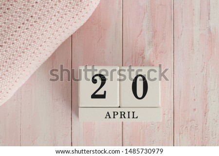 20 April Date on Cubes. Date on painted pink wood, next to baby blanket. Theme of baby due dates and birth dates. #1485730979