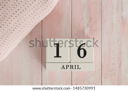 16 April Date on Cubes. Date on painted pink wood, next to baby blanket. Theme of baby due dates and birth dates. #1485730991