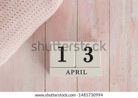 13 April Date on Cubes. Date on painted pink wood, next to baby blanket. Theme of baby due dates and birth dates. #1485730994