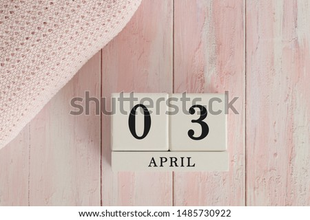 3 April Date on Cubes. Date on painted pink wood, next to baby blanket. Theme of baby due dates and birth dates. #1485730922