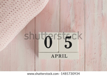 5 April Date on Cubes. Date on painted pink wood, next to baby blanket. Theme of baby due dates and birth dates. #1485730934