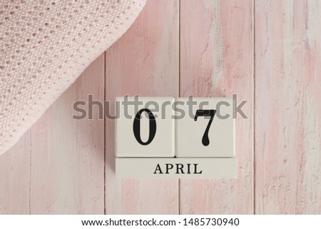 7 April Date on Cubes. Date on painted pink wood, next to baby blanket. Theme of baby due dates and birth dates. #1485730940