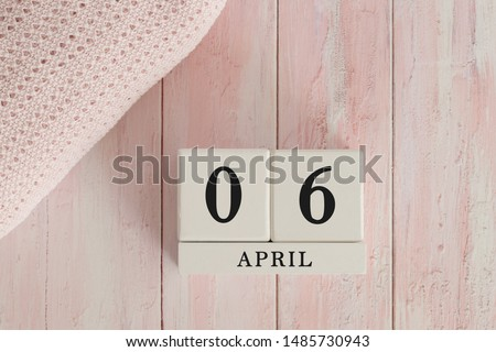 6 April Date on Cubes. Date on painted pink wood, next to baby blanket. Theme of baby due dates and birth dates. #1485730943