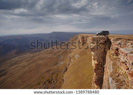 Сar on the edge of a rock cliff against a cloudy sky on a bright sunny day. Extreme travel and freedom. Danger may fall #1389788480