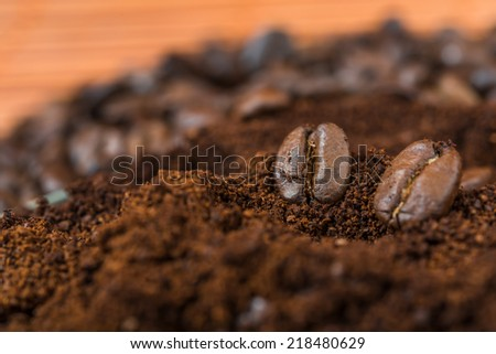 Arabic ground roasted coffee and coffee beans. Coffee beans and  ground coffee on brown background.