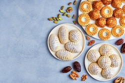 Arabic sweets. Traditional eid semolina maamoul or mamoul cookies with dates , walnuts and pistachio nuts  . Top view, copy space