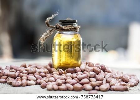[Arachis hypogaea] Raw Groundnut with groundnut oil on a gunny background.