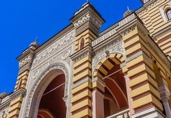 Arch above the entrance to Tbilisi Opera and ballet theatre, richly decorated with floral ornaments against the blue sky