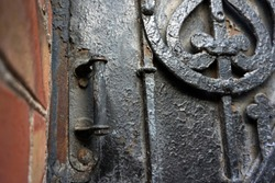 Architectural vintage background - old rusty black metal door with plates and aged metal door handle in the old red brick wall.
