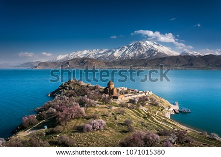 'Armenian Holy Cross Cathedral' surrounded by tree in blossom, in a middle of 'Akdamar Island' (Akdamr Adasi) #1071015380