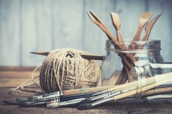 Art and craft tools. Artist's brushes, sculpturing set and pencil in glass jars on rustic background. Selective focus.