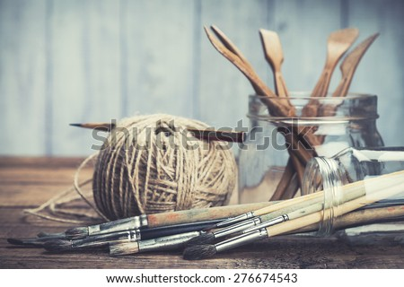Art and craft tools. Artist\'s brushes, sculpturing set and pencil in glass jars on rustic background. Selective focus.