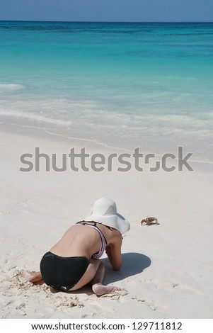 asia women play with crab on beach