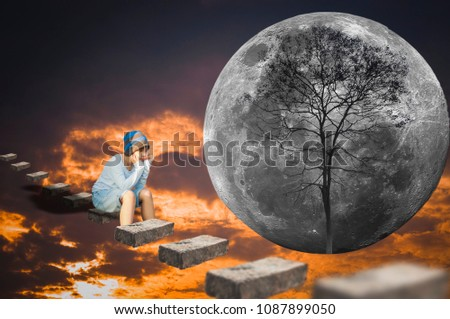 Stock Photo  Asian boy, sitting lonely on a brick floating in the sky, with a moon and trees as the background.