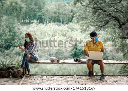 Asian couple wearing protective masks working at nature,Coronavirus COVID-19 disease protection.Conversation from a safe distance.Socialization restriction.Social distancing practice.