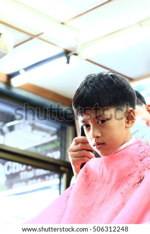 Asian Cute Boy Trying To Sit Still For A Barber Thailand Cute Child Scared And